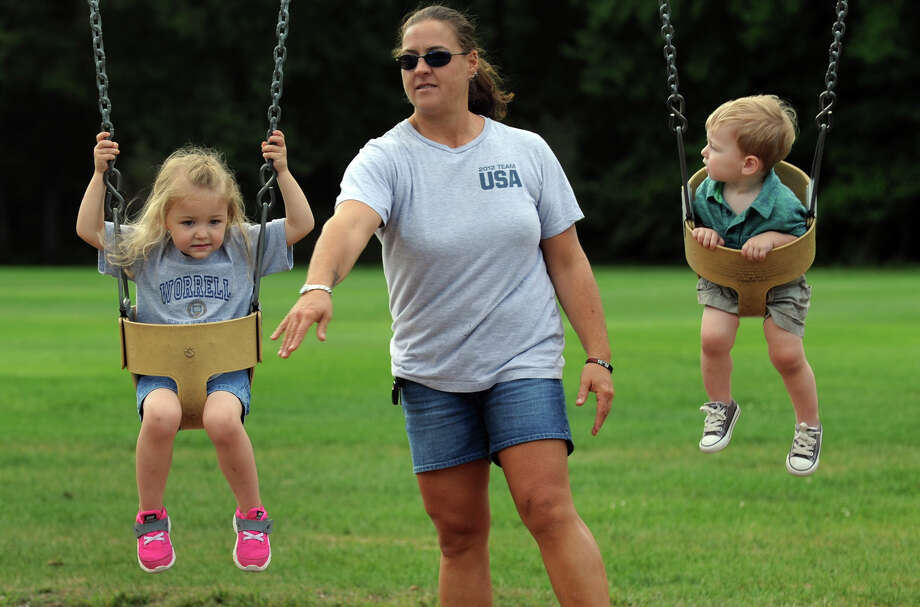 Babysitter Inga DeNunzio pushes Chloe Worrell, 3, left, and her brother Dean, 1, on the swing set at Twin Brooks Park in Trumbull, Conn. on Friday September 13, 2013. Photo: Christian Abraham / Connecticut Post