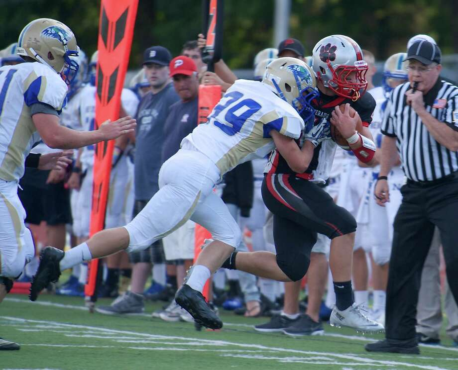 Newtown's Jimmy Leidlein, 39, drives Pomperaug's Bobby Tzepos, 4, out of bounds during a boys football game between Newtown High School and Pomperaug High School in Southbury, Conn. On Friday September 13, 2013. Photo: H John Voorhees III