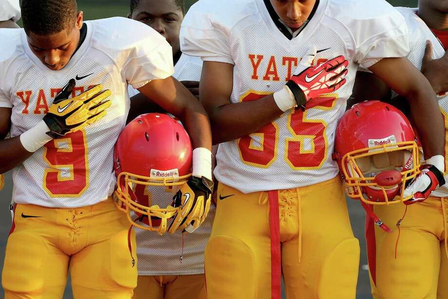Yates' Dalford Green #9 and Duante Fisher #65 listen to the National Anthem before playing against Madison. Photo: Thomas B. Shea, For The Chronicle / © 2013 Thomas B. Shea