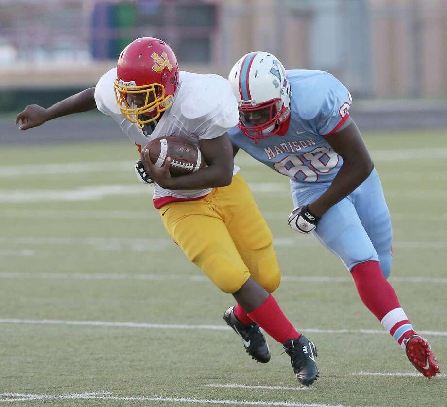 Yates' Bruce Wilson escapes the tackle of Madison's Nnanna Ezenwa. Photo: Thomas B. Shea, For The Chronicle / © 2013 Thomas B. Shea