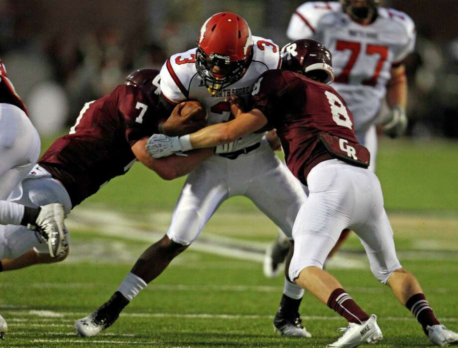 North Shore's Maciah Long (3) is tackled by Cinco Ranch's Nicholas Mika (7) and Grant Calfee (8) during the first half of a high school football game, Friday,  September 13, 2013 at Rhodes Stadium in Katy. Photo: Eric Christian Smith, For The Chronicle