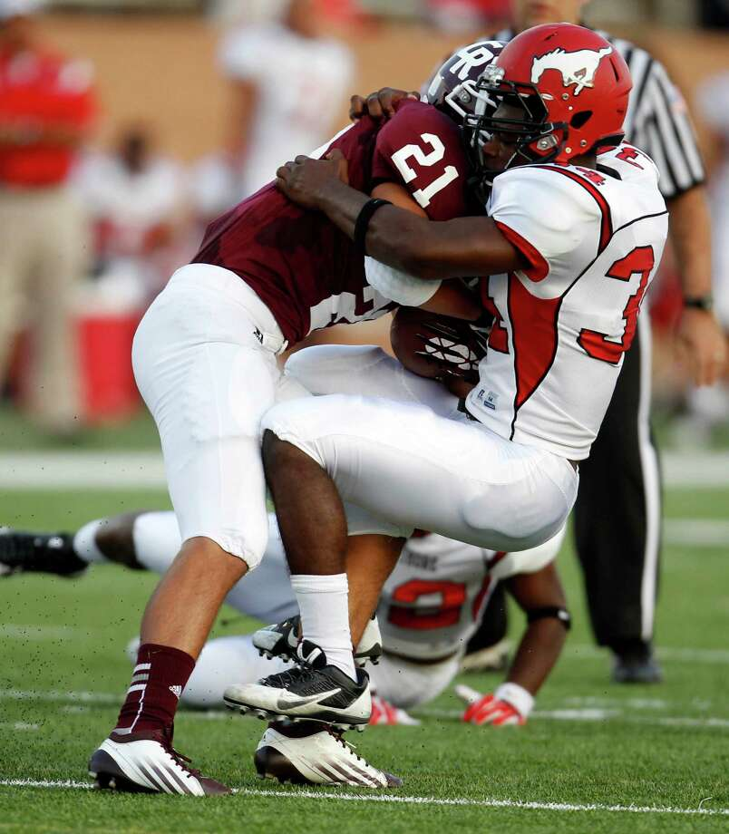 Cinco Ranch's Jonathan Lugo (21) is tackled by North Shore's John Joseph during the first half of a high school football game, Friday,  September 13, 2013 at Rhodes Stadium in Katy. Photo: Eric Christian Smith, For The Chronicle