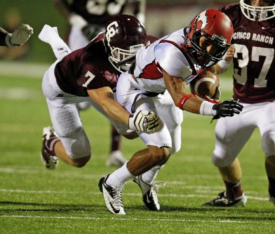 North Shore's Kevian DeLeon (2) tries to shake the tackle of Cinco Ranch's Nicholas Mika (7) during the second half of a high school football game, Friday, September 13, 2013 at Rhodes Stadium in Katy. Photo: Eric Christian Smith, For The Chronicle
