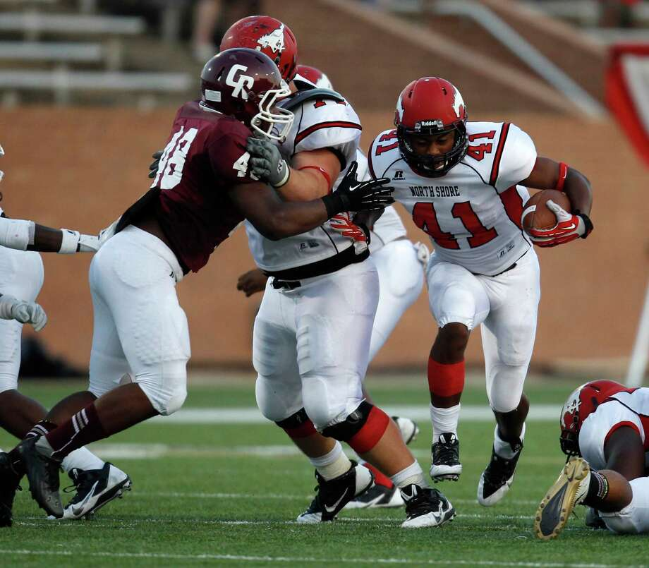 North Shore's Tristian Houston (41) runs the ball upfield past Cinco Ranch's Donovan Roberts (48) during the first half of a high school football game, Friday,  September 13, 2013 at Rhodes Stadium in Katy. Photo: Eric Christian Smith, For The Chronicle
