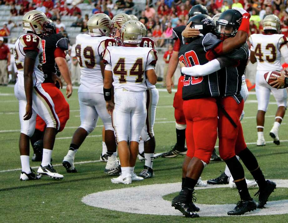 Langham Creek Lobos running back Christopher Williams, left, hugs quarterback Kyle Cutbirth after Cutbirth scored a touchdown during the first half of a football game against Cypress Woods at the Berry Center, Friday, Sept. 13, 2013, in Cypress. Photo: Cody Duty, Houston Chronicle / © 2013 Houston Chronicle
