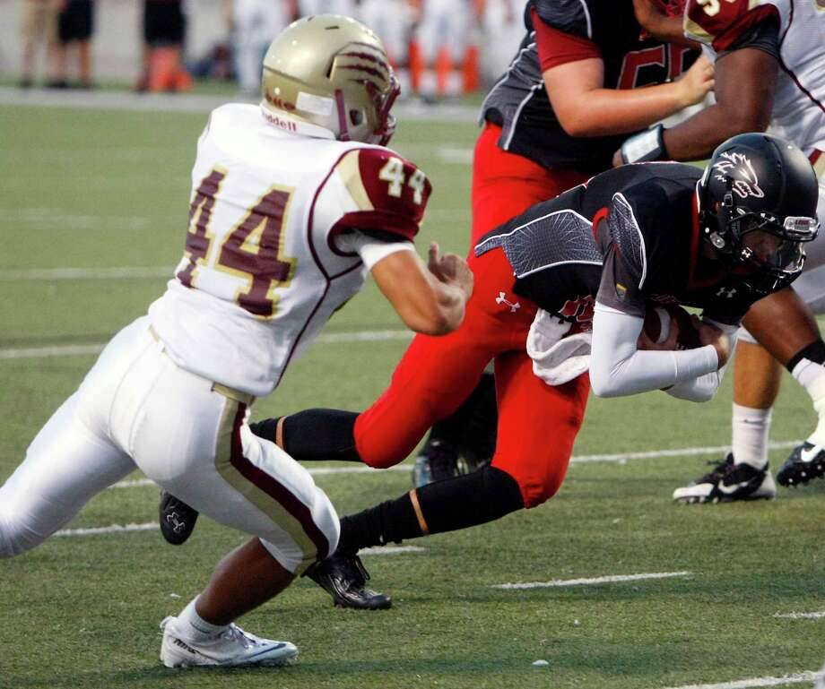 Langham Creek Lobos quarterback Kyle Cutbirth avoids a tackle from Cypress Woods linebacker Hector Larios, left, as scores a touchdown during the first half of a football game at the Berry Center, Friday, Sept. 13, 2013, in Cypress. Photo: Cody Duty, Houston Chronicle / © 2013 Houston Chronicle