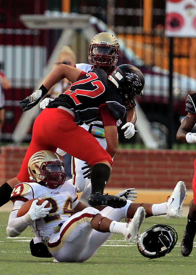 Langham Creek Lobos defensive back Keith Batista jumps over Cypress Woods Wildcats running back Samuel Stewart during the first half of a football game at the Berry Center, Friday, Sept. 13, 2013, in Cypress. Photo: Cody Duty, Houston Chronicle / © 2013 Houston Chronicle