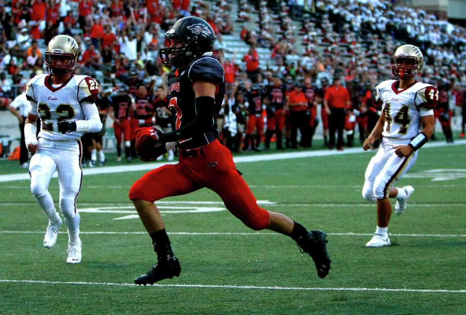 Langham Creek Lobos wide receiver Bryce Langan runs in a touchdown past Cypress Woods Wildcats Sam Dobbs, left, and Hector Larios, right, during the first half of a football game at the Berry Center, Friday, Sept. 13, 2013, in Cypress. Photo: Cody Duty, Houston Chronicle / © 2013 Houston Chronicle