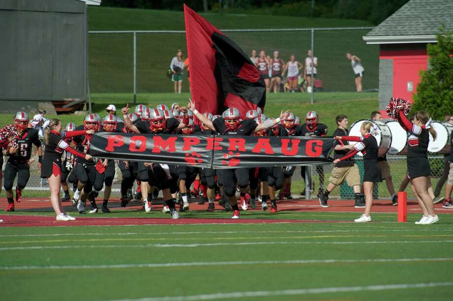 Pomperaug High School's boys football team runs on to the field before the start of their game with Newtown High School on Friday September 13, 2013, in Southbury, Conn. Photo: H John Voorhees III