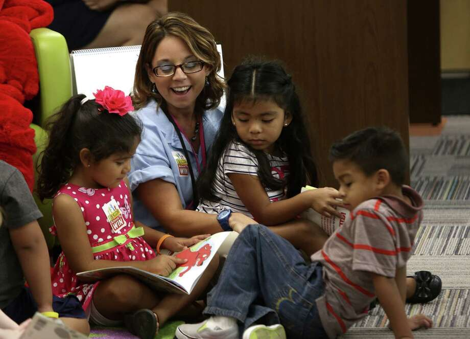Pre-K 4 SA instructor Christina Martinez reads with Alaliyah Zurita, Mackenzie Gonzalez, Raul Chavez IV and Maxine Spitzen as P16 Council Executive Director Judy McCormick, Councilman Rey Saldaña, NEISD Superintendent Brian Gottardy and others in gathered Friday kick off a national attendance awareness month. Photo: Helen L. Montoya / San Antonio Express-News