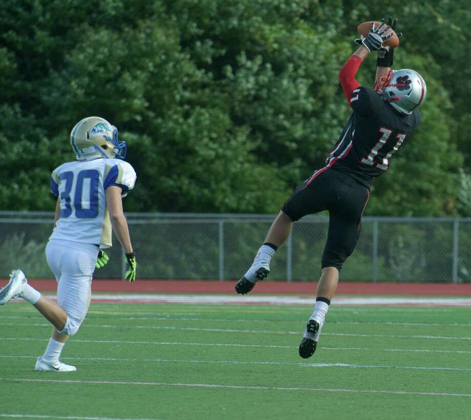 Pomperaug's Steve Croce, 11, goes up for a pass during Friday's football game between Newtown and Pomperaug High Schools in Southbury, Conn., on September 13, 2013. Photo: H John Voorhees III