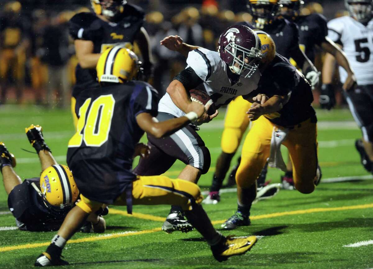 Burnt Hills' David Newell, center, carries the ball and sets up a touchdown during their football game against Troy on Friday, Sept. 13, 2013, at Troy High in Troy, N.Y. (Cindy Schultz / Times Union)