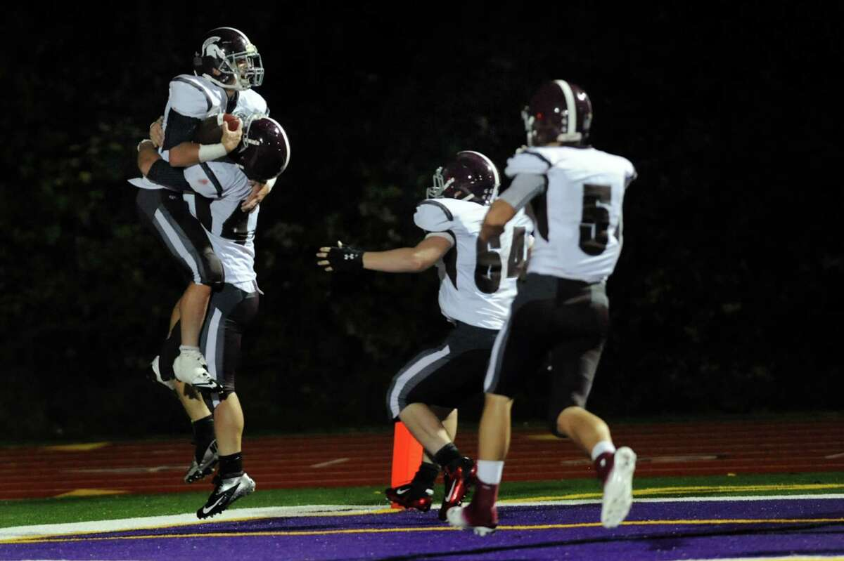 Burnt Hills Josh Quesada, left, celebrates his touchdown as teammate David Newell picks him up to win 18-12 over Troy in four overtimes during their football game on Friday, Sept. 13, 2013, at Troy High in Troy, N.Y. (Cindy Schultz / Times Union)