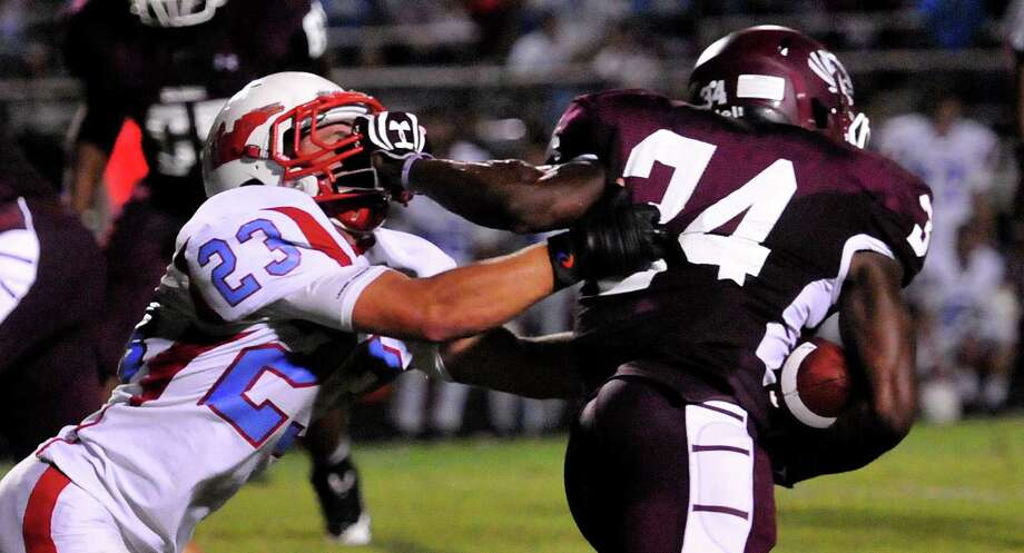 Floyd Spearman grabs Ian Stoute's mask during the game Friday night. Photo: Cassie Smith