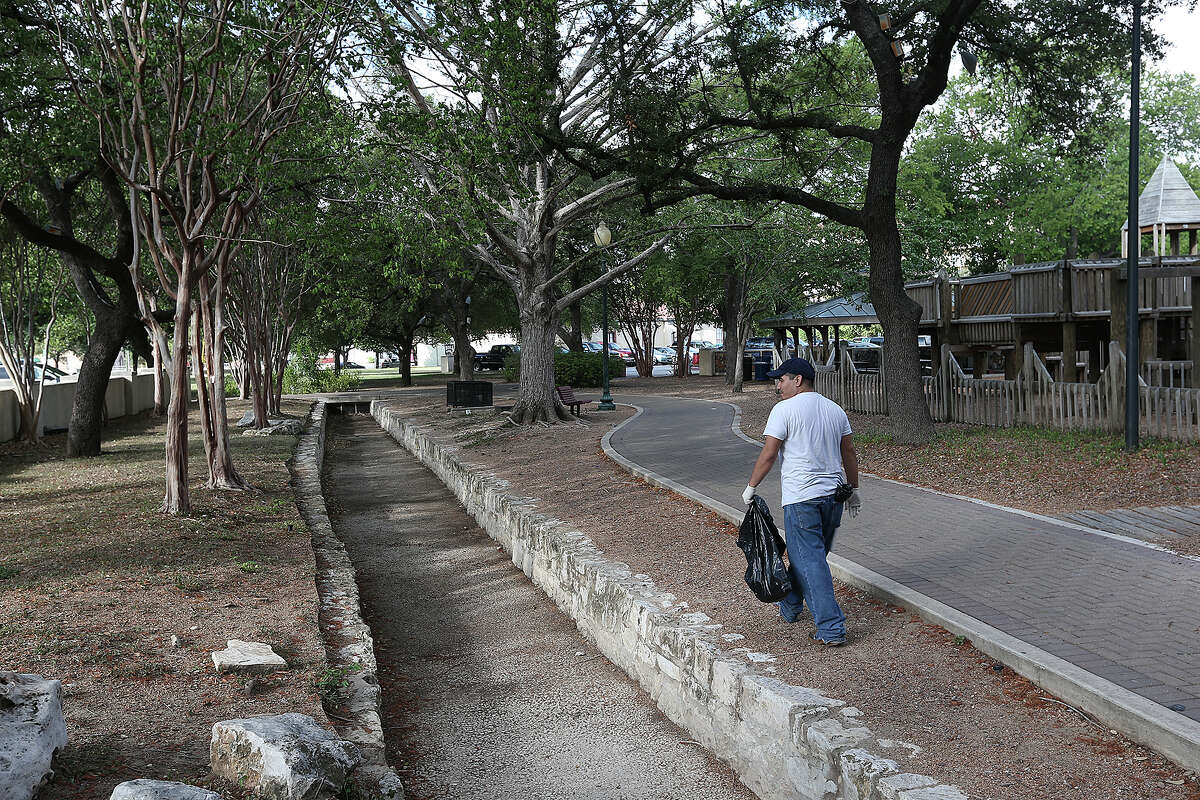 Volunteer Felipe Cerda cleans up around a section of the old Acequia Madre de Valero at HemisFair Park, Sunday, Sept. 8, 2013. The City of San Antonio is planning on redeveloping the area to include housing. According to a plaque by the acequia, it was built in the early 1700's and the HemisFair section was restored in 1968.