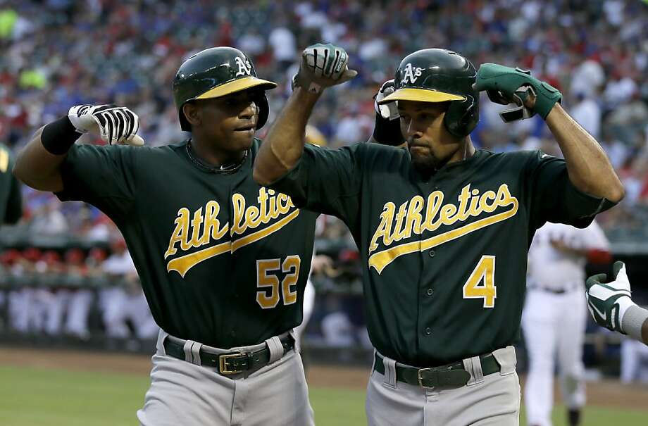 Oakland Athletics' Yoenis Cespedes and Coco Crisp (4) flex their muscles as they walk back to the dugout following Cespedes' three-run home run that came off a pitch from Texas Rangers' Derek Holland in the first inning of a baseball game, Friday, Sept. 13, 2013, in Arlington, Texas. The shot scored Crisp and Josh Donaldson. (AP Photo/Tony Gutierrez) Photo: Tony Gutierrez, Associated Press