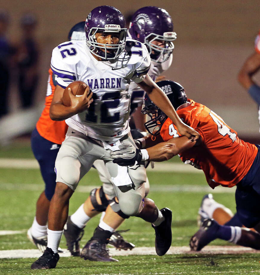 Warrior quarterback Jordan Sneed gets by Chase Guillory as he tries the middle for some yards as Warren plays Brandeis at Farris Stadium on September 13,  2013. Photo: For The San Antonio Express-News