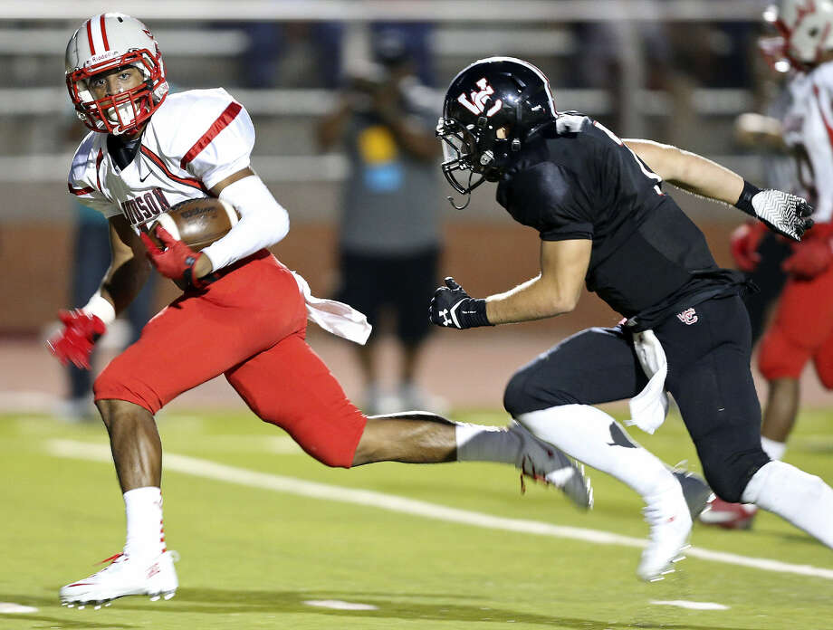 Judson's Andre Wilson heads for a score ahead of Churchill's Matt Ruiz during the first half at Heroes Stadium. Photo: Photos By Edward A. Ornelas / San Antonio Express-News