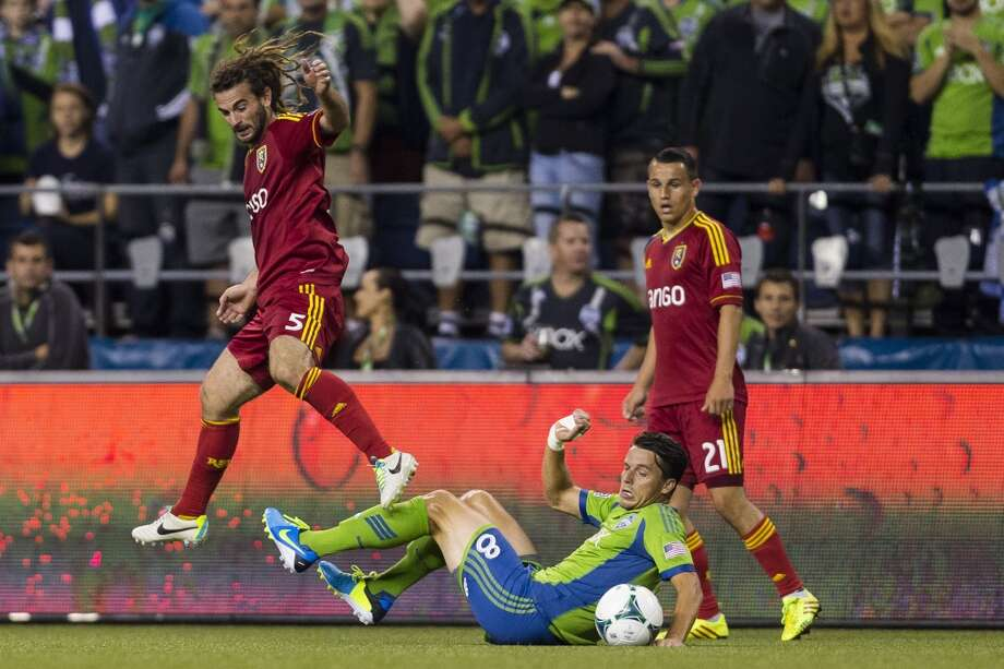 Marc Burch, center, falls while making his way downfield with the ball during the first half of a game Friday, September 13, 2013, at CenturyLink Field in Seattle. The Sounders led Real Salt Lake 2-0 at the half. With over 52,000 tickets distributed, the Sounders put their 12-game home unbeaten streak on the line during the face-off with Real Salt Lake. (Jordan Stead, seattlepi.com) Photo: JORDAN STEAD, SEATTLEPI.COM