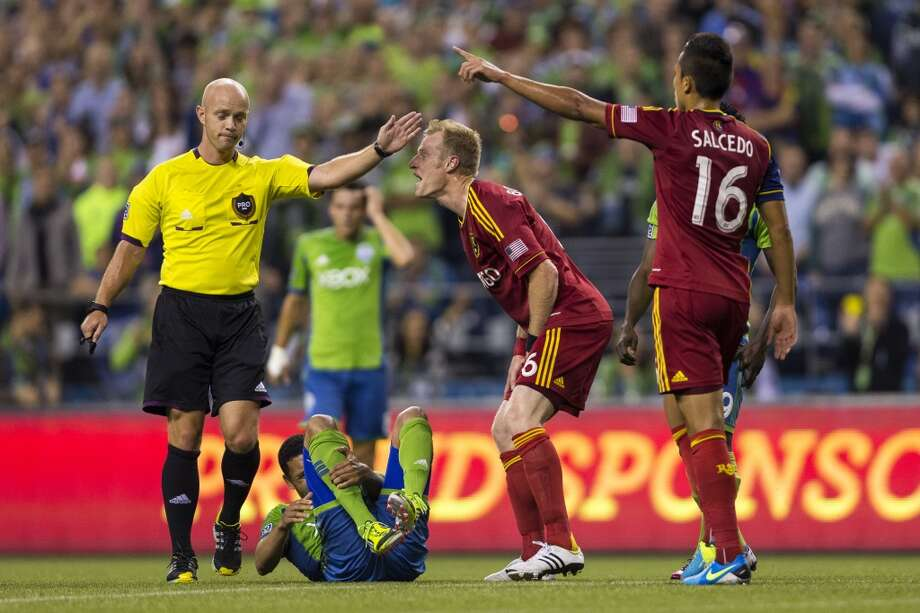 A referee interferes with injured players after a mid-air collision during the first half of a game Friday, September 13, 2013, at CenturyLink Field in Seattle. The Sounders led Real Salt Lake 2-0 at the half. With over 52,000 tickets distributed, the Sounders put their 12-game home unbeaten streak on the line during the face-off with Real Salt Lake. (Jordan Stead, seattlepi.com) Photo: JORDAN STEAD, SEATTLEPI.COM