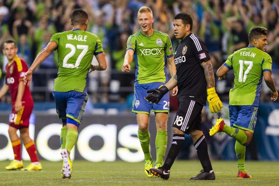 Andy Rose, center, reacts to a goal for his team by Lamar Neagle, left, during the first half of a game Friday, September 13, 2013, at CenturyLink Field in Seattle. The Sounders led Real Salt Lake 2-0 at the half. With over 52,000 tickets distributed, the Sounders put their 12-game home unbeaten streak on the line during the face-off with Real Salt Lake. (Jordan Stead, seattlepi.com) Photo: JORDAN STEAD, SEATTLEPI.COM