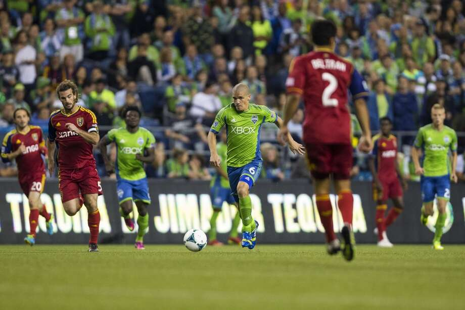 Osvaldo Alonso, center, dribbles through the midfield during the second half of a game Friday, September 13, 2013, at CenturyLink Field in Seattle. The Sounders beat Real Salt Lake 2-0. With over 52,000 tickets distributed, the Sounders put their 12-game home unbeaten streak on the line during the face-off with Real Salt Lake. (Jordan Stead, seattlepi.com) Photo: JORDAN STEAD, SEATTLEPI.COM
