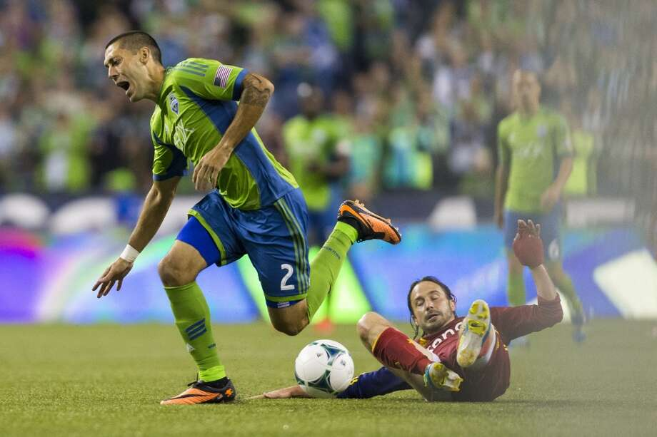 Clint Dempsey, left, falls while attempting to push through Real Salt Lake defense on his way to the goal during the second half of a game Friday, September 13, 2013, at CenturyLink Field in Seattle. The Sounders beat Real Salt Lake 2-0. With over 52,000 tickets distributed, the Sounders put their 12-game home unbeaten streak on the line during the face-off with Real Salt Lake. (Jordan Stead, seattlepi.com) Photo: JORDAN STEAD, SEATTLEPI.COM