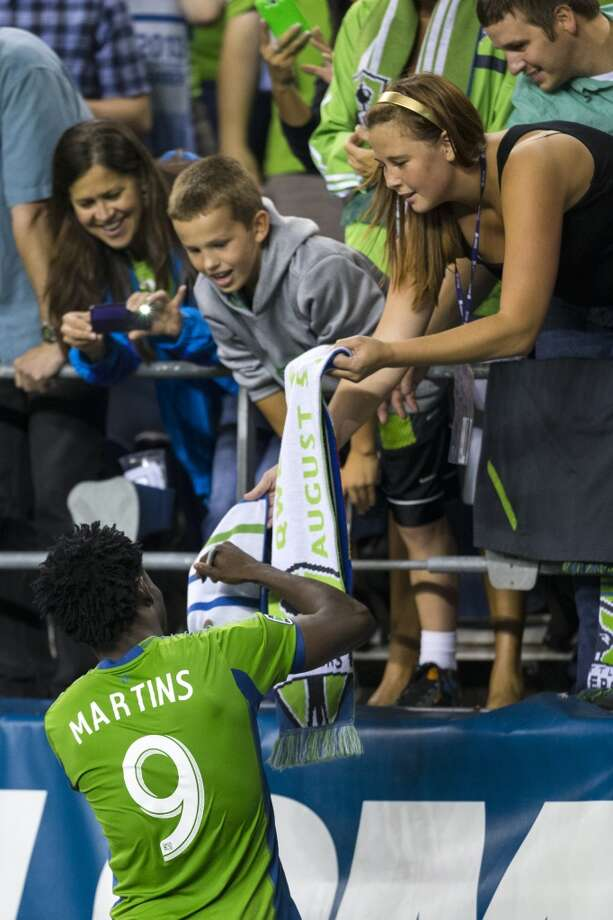 Obafemi Martins signs scarves for fans after beating Real Salt Lake 2-0 following the second half of a game Friday, September 13, 2013, at CenturyLink Field in Seattle. With over 52,000 tickets distributed, the Sounders put their 12-game home unbeaten streak on the line during the face-off with Real Salt Lake. (Jordan Stead, seattlepi.com) Photo: JORDAN STEAD, SEATTLEPI.COM