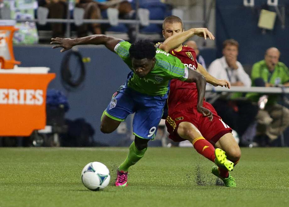 Seattle Sounders forward, Obafemi Martins, left, takes a fall during the first half of a game Friday, September 13, 2013, at CenturyLink Field in Seattle. With over 52,000 tickets distributed, the Sounders put their 12-game home unbeaten streak on the line during the face-off with Real Salt Lake. Seattle won 2-0. (Sy Bean, seattlepi.com) Photo: SEATTLEPI.COM