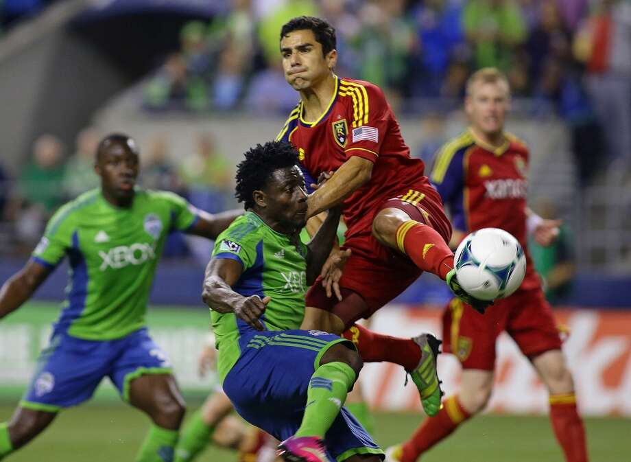 Seattle Sounder forward, Obafemi Martins, collides with Tony Beltran of Real Salt Lake during the second half of the game Friday, September 13, 2013, at CenturyLink Field in Seattle. With over 52,000 tickets distributed, the Sounders put their 12-game home unbeaten streak on the line during the face-off with Real Salt Lake. The Sounders won 2-0. (Sy Bean, seattlepi.com) Photo: SEATTLEPI.COM