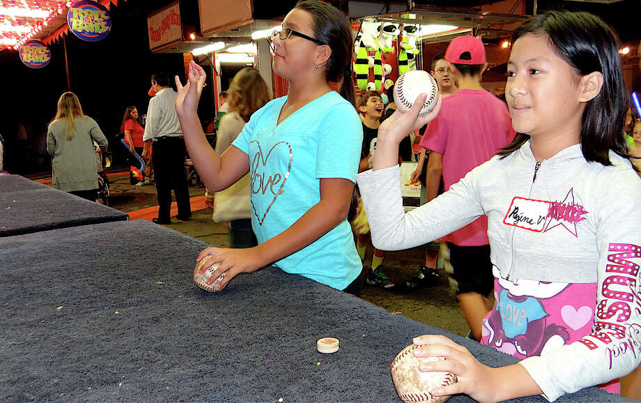 Reina Valenzuela, 11, and Viviana Mora, 10, toss softballs for prizes Friday at SeptemberFest. Photo: Mike Lauterborn / Fairfield Citizen contributed