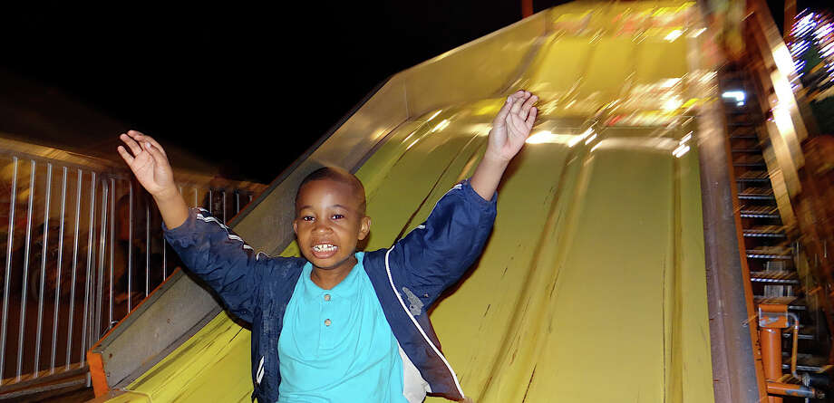 Nathan Christoph, 8, flie down the Super Slide on the Friday opening night of SeptemberFest at Assumption parish. Photo: Mike Lauterborn / Fairfield Citizen contributed