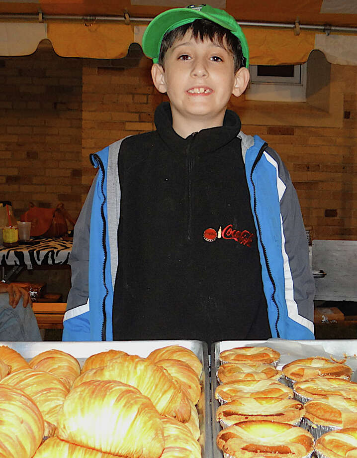 Jack Spielman, 9, helps staff Luigi's Bakery table on Friday at SeptemberFest. Photo: Mike Lauterborn / Fairfield Citizen contributed