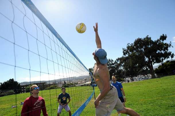 Evan Earust jumps up to spikes the ball during a game of volleyball with friends at the Fort Mason Great Meadow in San Francisco, California, Saturday August 17, 2013.