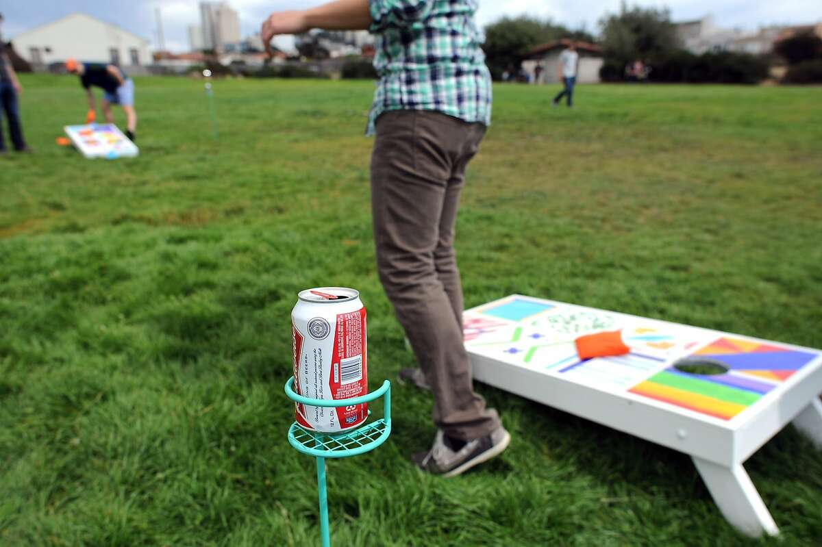 A can of beer sits in a caddie as people play corn hole at the Fort Mason Great Meadow in San Francisco, California, Saturday August 17, 2013.