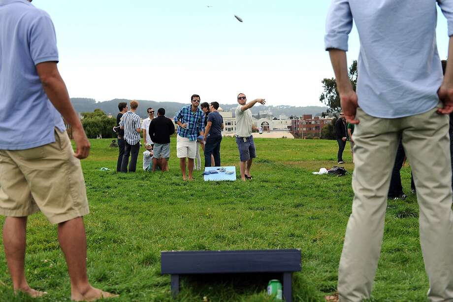 James G. and Aaron Alcorn, right, play a game of corn hole with friends at the Fort Mason Great Meadow in San Francisco, California, Saturday August 17, 2013. Photo: Michael Short, Special To The Chronicle