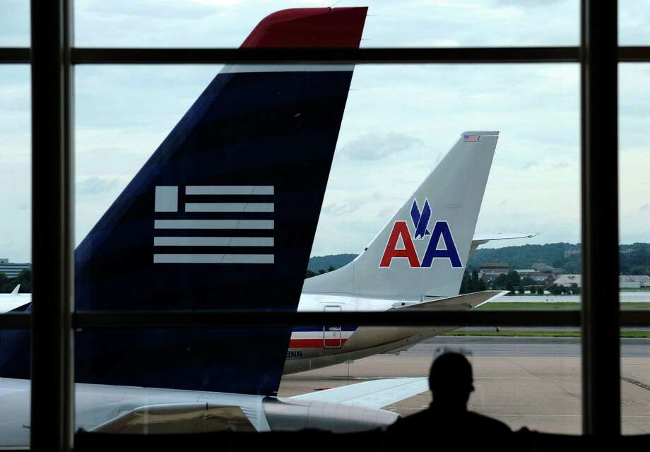 FILE-  In this Tuesday, Aug. 13, 2013, file photo, an American Airlines plane and a US Airways plane are  parked at Washington's Ronald Reagan National Airport in Washington.American Airlines and US Airways say that the government's opposition to their planned merger shows that it doesn't understand the airline industry. (AP Photo/Susan Walsh, File) Photo: Susan Walsh, STF / AP