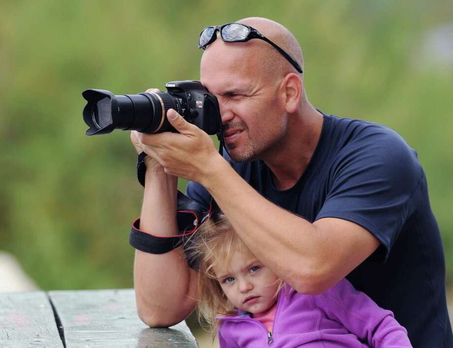 With his daughter, Catelyn, 2, tucked between his arms, Kris Shockley of Greenwich, takes a photo of the Manhattan skyline from Greenwich Point, Saturday, Sept. 14, 2013. Photo: Bob Luckey / Greenwich Time