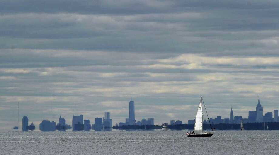 A sailboat makes its way across Long Island Sound with the Freedom Tower, center, and the Manhattan skyline visible in the background, as seen from Greenwich Point, Saturday, Sept. 14, 2013. Photo: Bob Luckey / Greenwich Time
