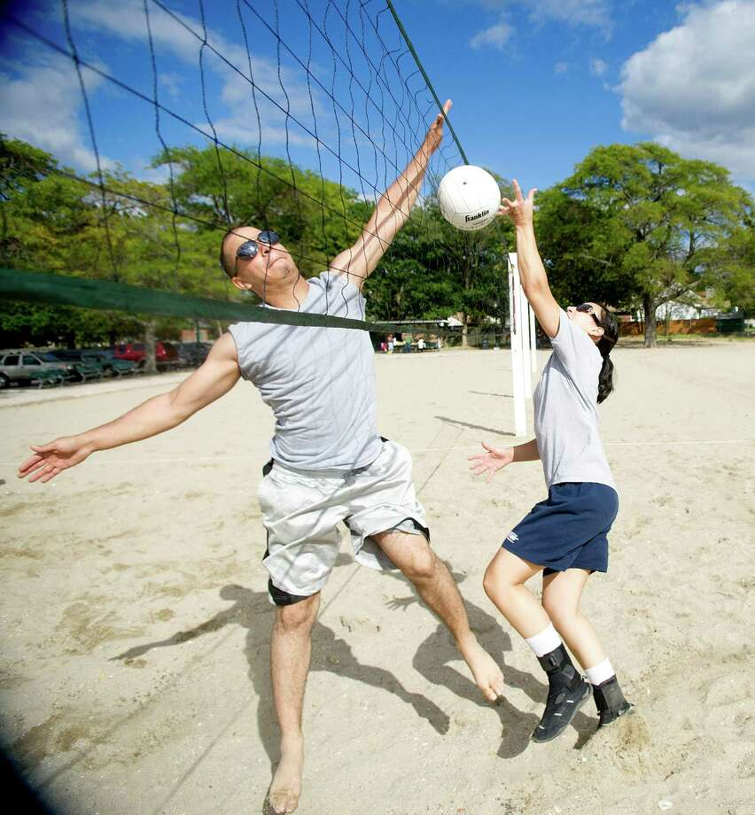 Abner Valdes, left, and Mariela Molina, right, play volleyball at Cummings Beach in Stamford, Conn., on Saturday, Sept. 14, 2013. Photo: Lindsay Perry / Stamford Advocate