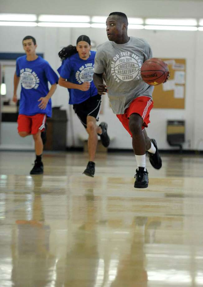 Warren Cummings, 17, of Bridgeport, controls the ball during the first game of the Christian Basketball League Saturday Sept. 14, 2013 at the Cardinal Shehan Center in Bridgeport, Conn. Photo: Autumn Driscoll / Connecticut Post
