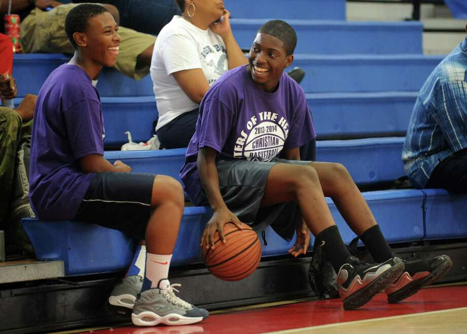Mikey Baldwin, 15, of New Haven, left, and Shaune West, 16, of Bridgeport, from Cathedral of Praise, watch the first game of the Christian Basketball League Saturday Sept. 14, 2013 at the Cardinal Shehan Center in Bridgeport, Conn. Photo: Autumn Driscoll / Connecticut Post