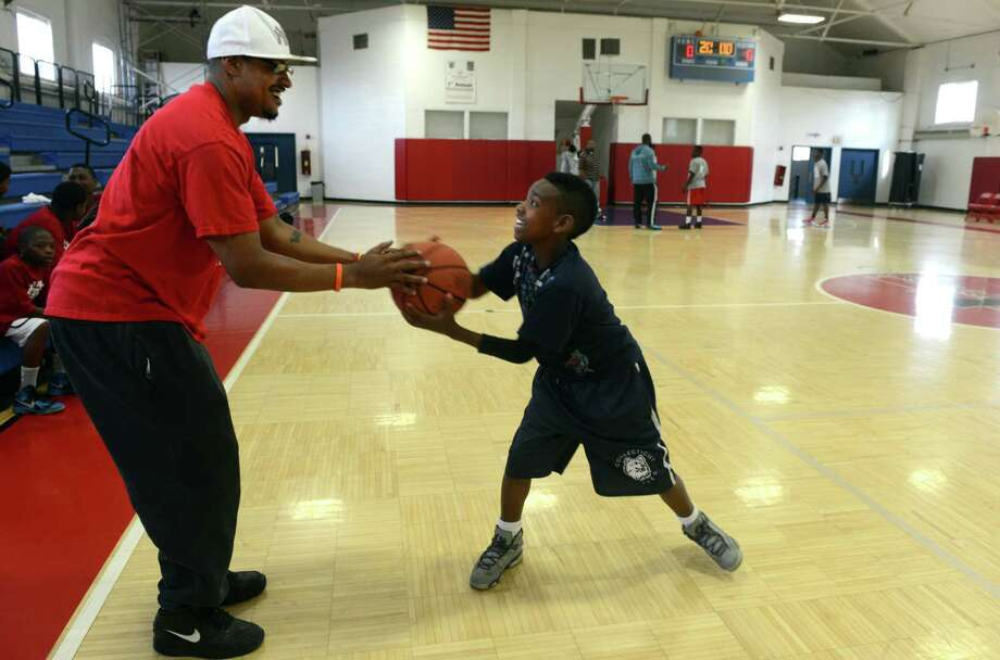 Kyle Gray, of Bridgeport, a coach for the Cathedral of Praise team, squares off with his son Joseph, 10, before the start of the first game of the Christian Basketball League Saturday Sept. 14, 2013 at the Cardinal Shehan Center in Bridgeport, Conn.  The league was organized by local churches to keep kids out of trouble and to help them meet other kids in a safe environment. Photo: Autumn Driscoll / Connecticut Post