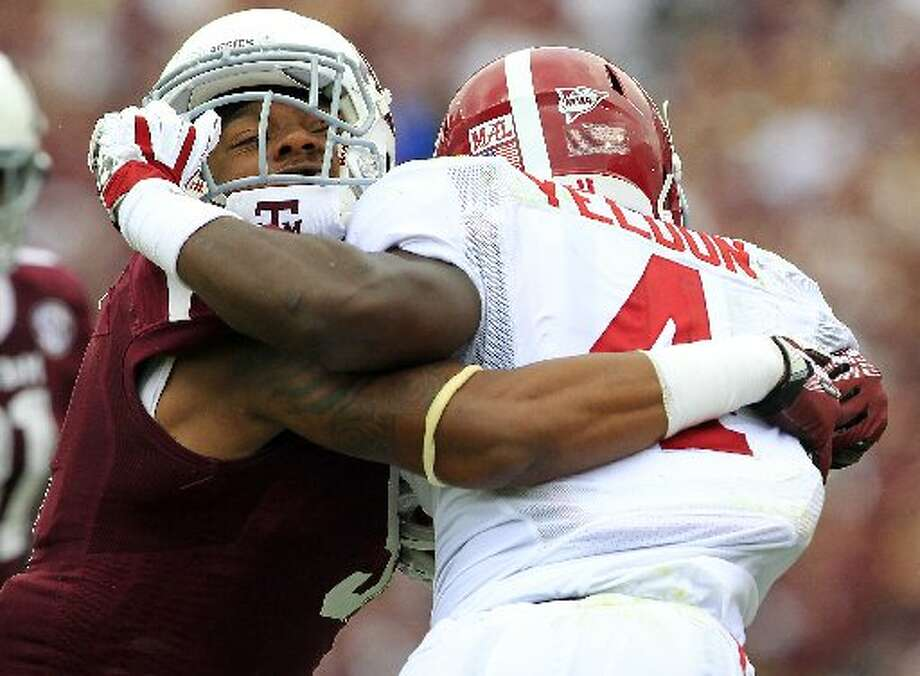 A Texas A&M defender tries to wrap up Alabama running back T.J. Yeldon. Photo: Cody Duty, Houston Chronicle