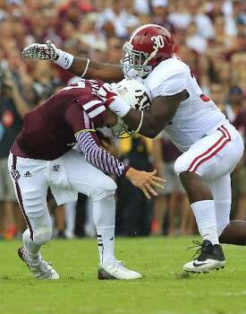 Texas A&M quarterback Johnny Manziel is wrapped up by an Alabama defender. Photo: Cody Duty, Houston Chronicle