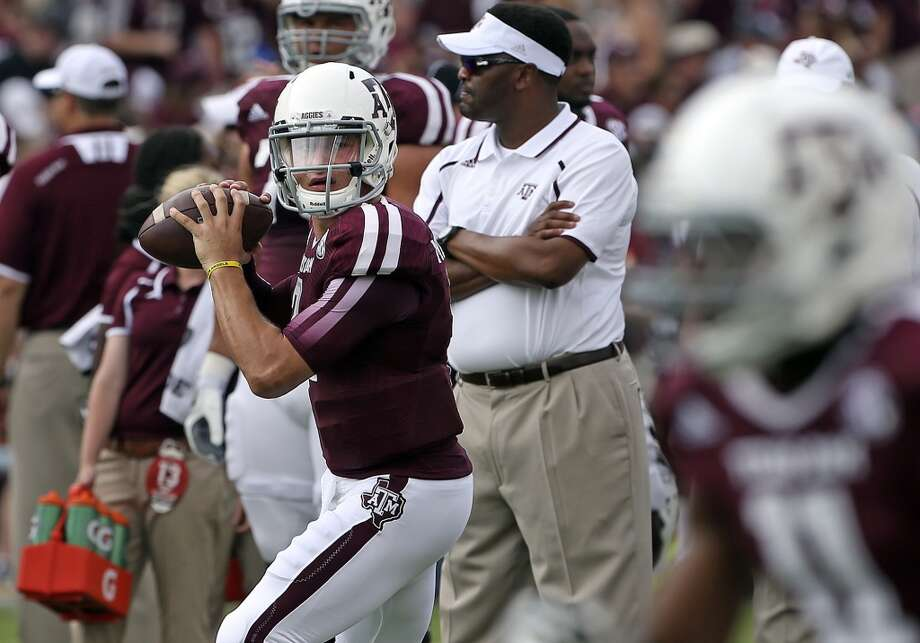 Aggie quarterback Johnny Manziel warms up in front of his coach Kevin Sumlin before Texas A&M hosts Alabama at Kyle Field in College Station on September 14,  2013.