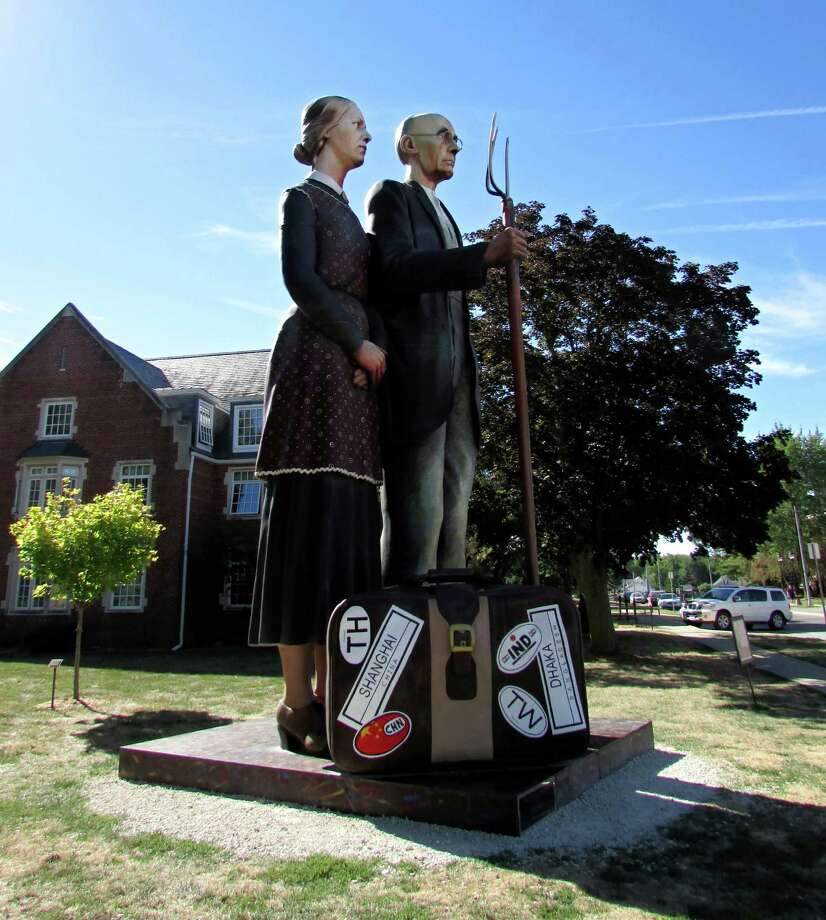 "A 25-foot-tall sculpture called ""God Bless America"", seen Saturday Sept. 14, 2013 in Indianola, Iowa depicts the famous ""American Gothic"" painting by Iowa native Grant Wood. Seward Johnson's 30,000-pound sculpture arrived on the Simpson College campus earlier this summer and remain there for six months. The sculpture required multiple cranes and four days to assemble. Photo: Josh Baugh, San Antonio Express-News / © 2013 San Antonio Express-News"