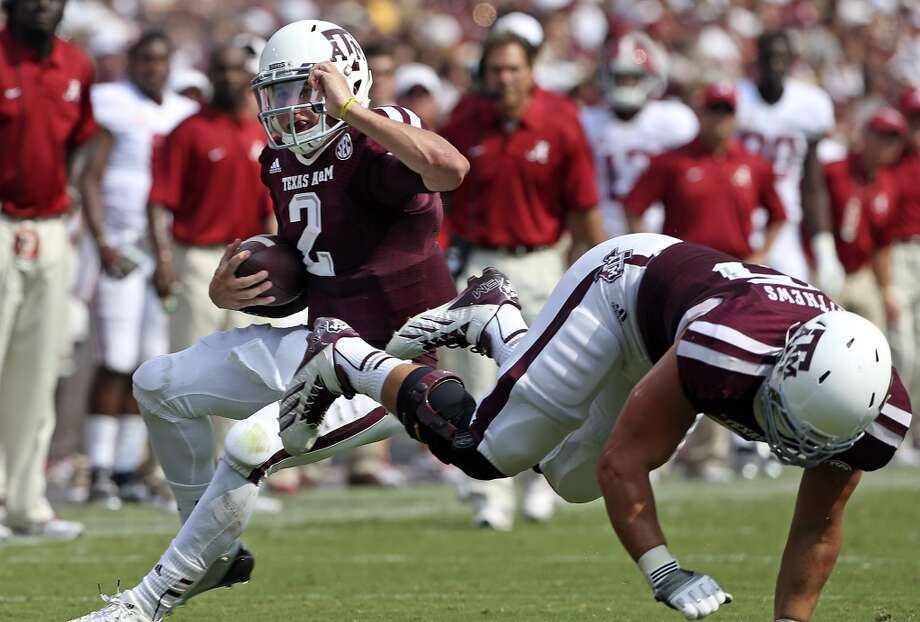 Aggie quarterback Johnny Manziel follows a block on the right side as Texas A&M hosts Alabama at Kyle Field in College Station on September 14,  2013.