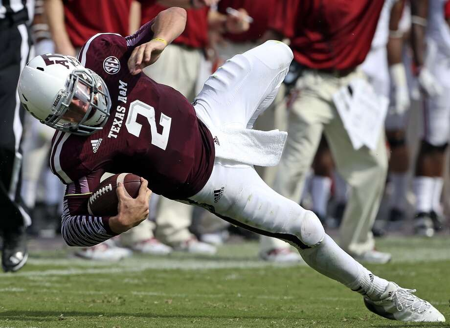 Aggie quarterback Johnny Manziel stretches for more yards as  Texas A&M hosts Alabama at Kyle Field in College Station on September 14,  2013.