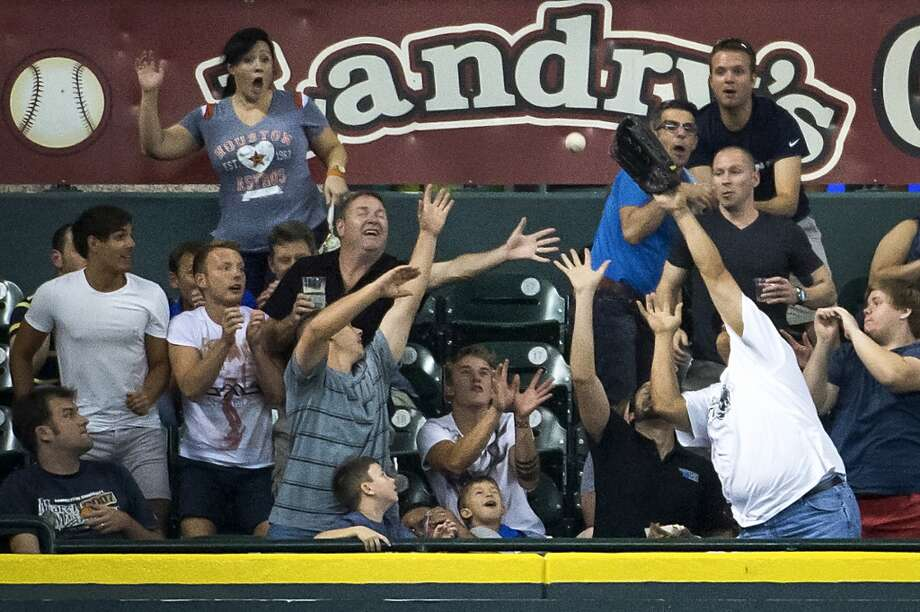 Fans in the Crawford Box at Minute Maid Park try to catch a home run hit by Astros second baseman Jose Altuve during the third inning. Photo: Smiley N. Pool, Houston Chronicle